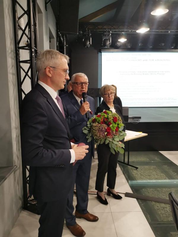 Stoją od lewej: Arkadiusz Ptak - burmistrz Pleszewa, Piotr Hasiński - były burmistrz odznaczony tytułem, Adela Grala-Kałużna - Przewodnicząca Rady Miejskiej w Pleszewie