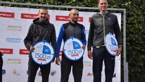na pierwszym stopniu stoi trójka mężczyzn - zwycięzców Biegu Pzemysława na dystansie 5 km; w ręku trzymają nagrody