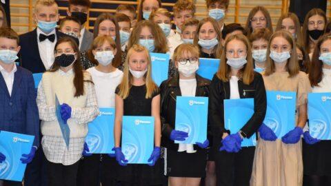 Grupa kilkunastu uczniów trzymających w ręku niebieskie teczki ze stypendiami burmistrza