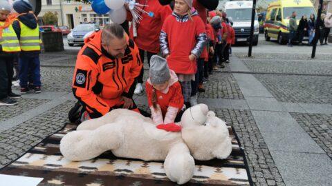 Przedszkolak-dziewczynka wykonuje reanimacje serca na maskotce, obok ratownik medyczny, w tle inne dzieci