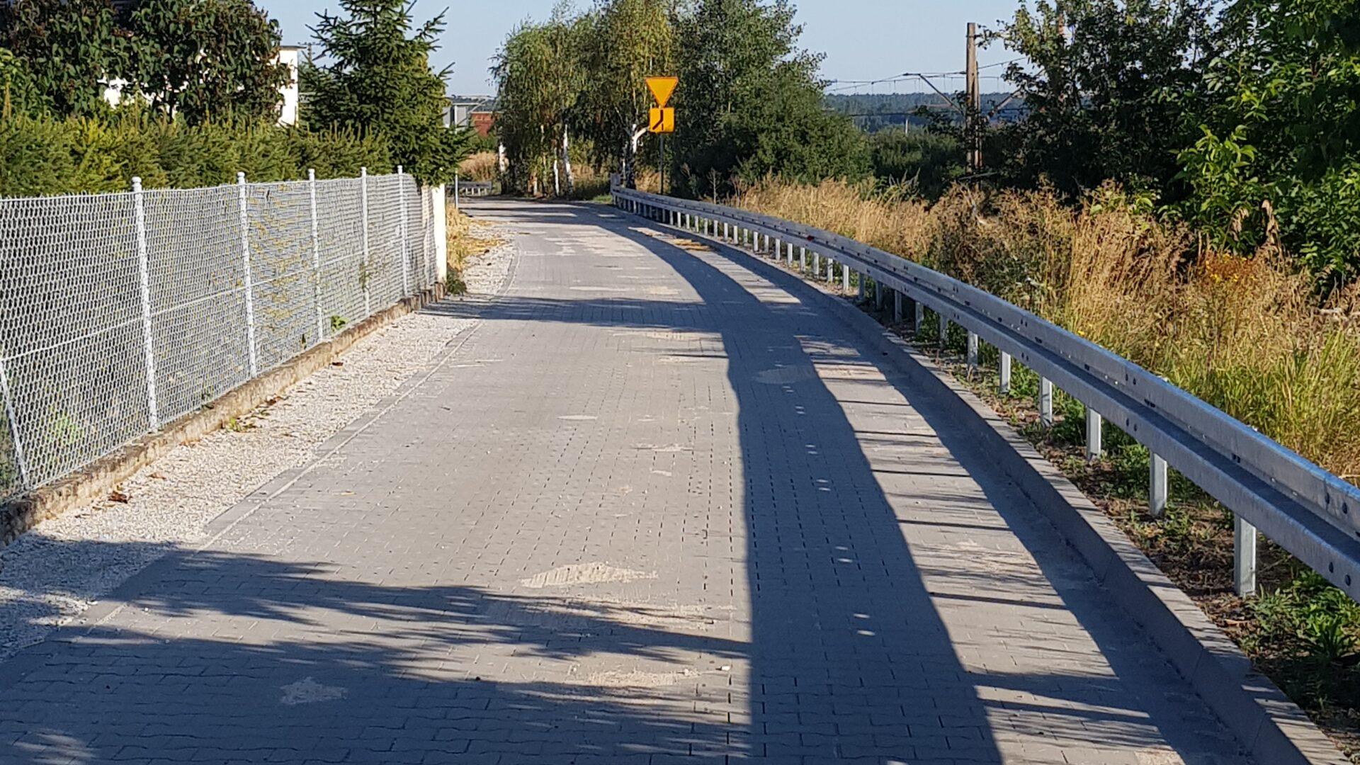 droga z kostki brukowej, po prawej stronie bariera ochronna, po lewej stronie ogrodzenie