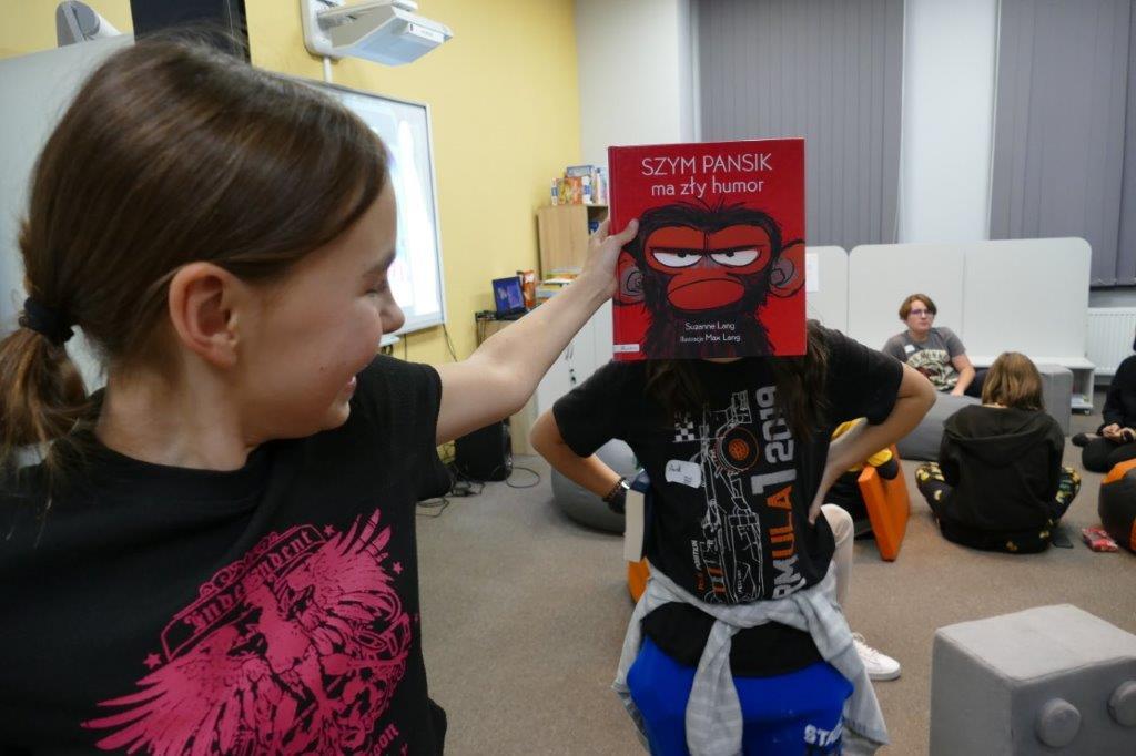 dziewczynka trzymająca książkę, która zasłania twarz chłopca tworząć tzw. sleeveface czyli ubieranie się w książkę